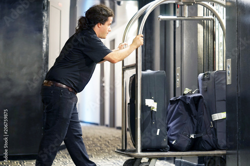 Fotografie, Obraz  Closeup many suitcases on hotel luggage cart moving by bell boy
