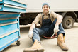 Portrait of young handsome male automotive technician sitting against truck in service garage and smiling at camera