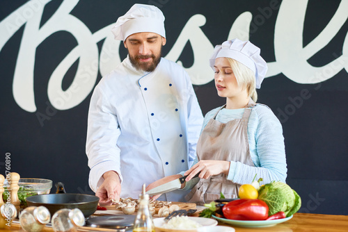 Chef explaining to woman the recipe of the dish