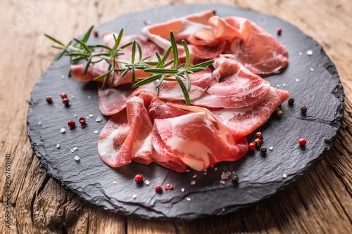Coppa di Parma ham on slate board with rosemary salt and pepper
