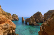 Rocky cliffs and grottoes in Algarve, Portugal. Cliffs and turquoise sea waters on a warm spring morning.
