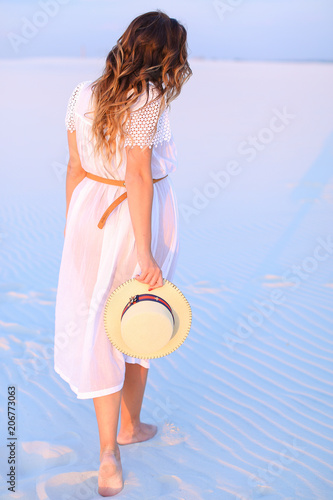 Láminas  Back view of standing young woman on white blue sand and keeping hat
