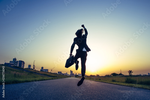 朝日にむかってジャンプするビジネスマン Poster