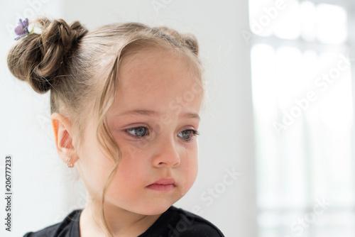 Photo  Beautiful sad little girl crying, on background white window