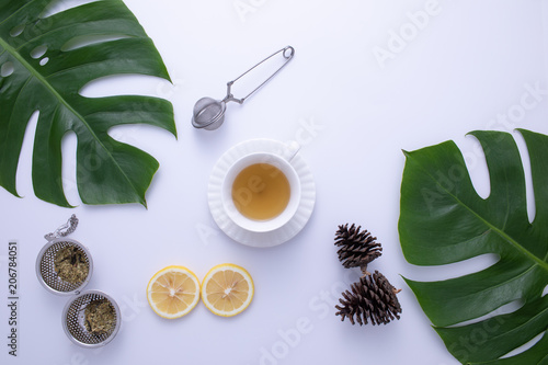 Fotografia, Obraz  A glass of hot tea with fruit and leaves decorated on white background