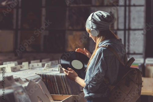 Spoed Foto op Canvas Muziekwinkel Young girl listening to music on headphones