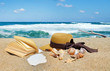 Book with Straw Hat and Seashells at the Summer Beach