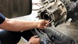 Close up of hands working on truck axel for repair