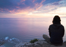 A Young Woman Watching A Beautiful Sunset Over The Ocean