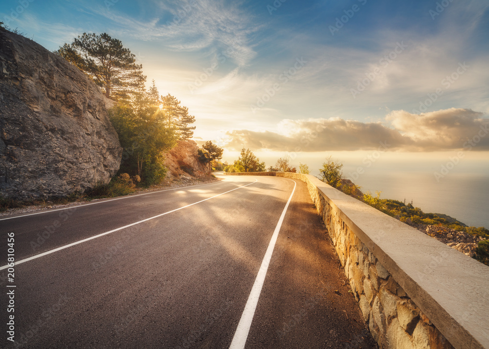 Fototapeta Mountain road at sunset in Europe. Landscape with rocks, sunny sky with clouds and beautiful asphalt road in the evening in summer. Colorful travel background. Highway in mountains. Transportation