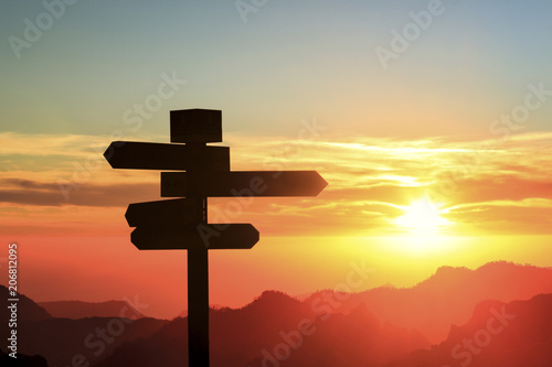 Silhouette of a signpost in a colorful sunset Fotobehang