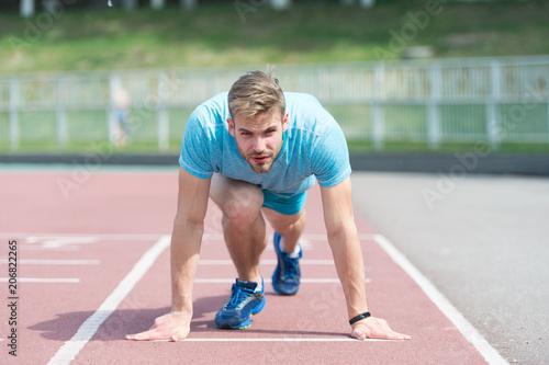 Fotografía  Man runner on start position at stadium
