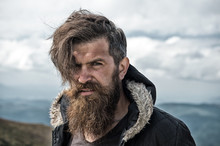 Man With Brutal Bearded Appearance, Brutal Unshaven Man Looks Untidy. Man With Long Beard And Mustache Wears Jacket. Hipster On Strict Face With Beard Looks Brutally While Hiking. Hermit Concept