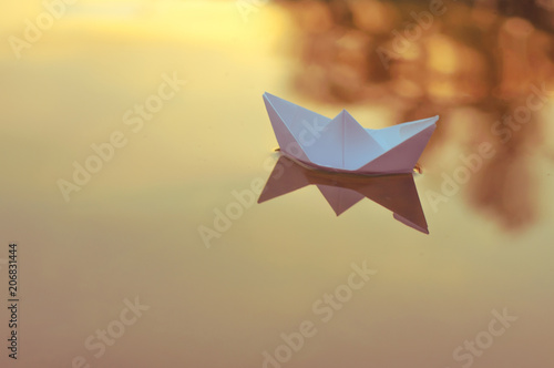 Obraz na plátně Paper origami boat floats on the surface of the water at sunset or dawn