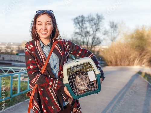 Fotografie, Obraz  A woman is transporting a cat in a special plastic cage or carrying bag to a vet