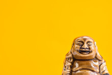 Ceramic Statue Of Laughing Buddha On Bright Orange Background. Buddhism Religious Symbol. Minimalist Inspirational Image With Copy Space For Quotes.