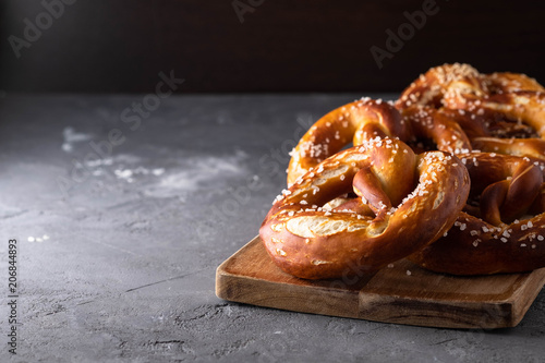 Freshly baked homemade soft pretzel with salt on rustic table Canvas Print