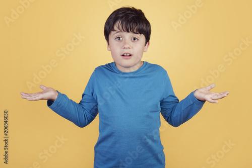 Fényképezés  niño confuso que pregunta sobre fondo amarillo