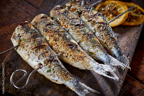 Fototapeta Four spicy grilled fresh fish on skewers obraz