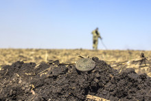 The Old Lost Coin In The Field, On The Blurred Background Of The Treasure Hunter With A Metal Detector