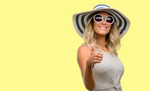 Young Woman Wearing Sunglasses And Summer Hat Smiling Broadly Showing Thumbs Up Gesture To Camera, Expression Of Like And Approval