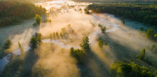Foggy Summer Morning. Misty Aerial Landscape. White Fog Over Green Meadow Near River In Morning Sunlight From Above.