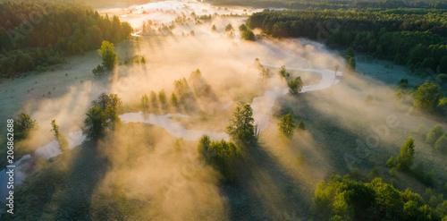 Mglisty letni poranek. Mglisty krajobraz z lotu ptaka. Biała mgła nad zieloną łąką w pobliżu rzeki w świetle słonecznym rano z góry.