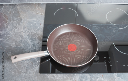 Modern electric stove with empty frying pan