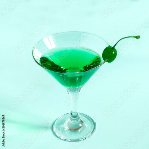 Fotobehang Alcohol Green cocktail with maraschino cherry in martini glass