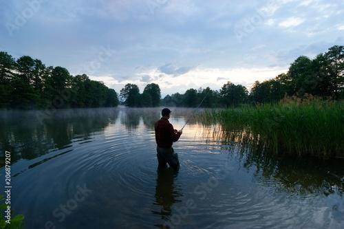 Printed kitchen splashbacks Fishing fisherman standing in the lake and catching the fish during sunrise