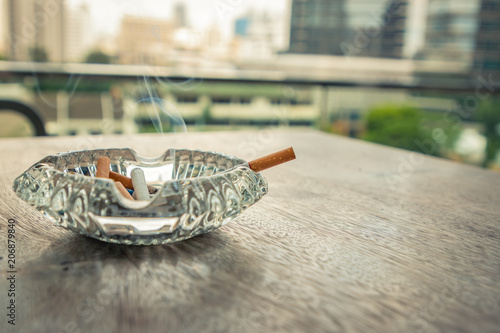 Photo Smoking cigarette in ashtray on the wood table