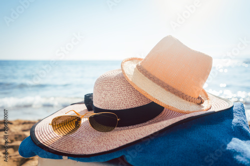 Fotografia  Sun hats and glasses on beach in the sand by the water