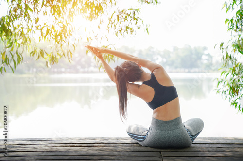 Young woman doing yoga in morning park near lake