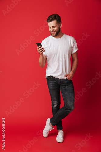 Happy young man using mobile phone.