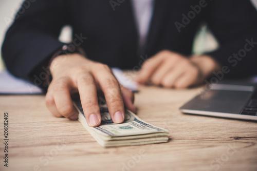 Fotomural  Hands close up : Man offering batch of hundred dollar bills