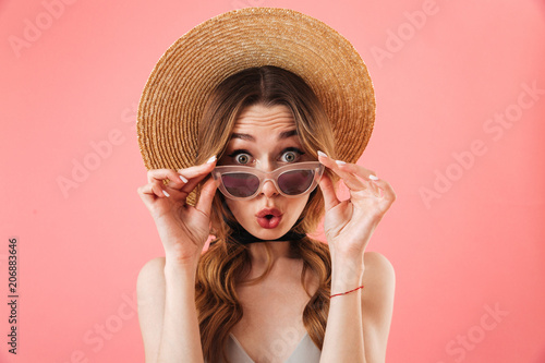 Poster  Surprised confused brunette woman wearing in dress and hat