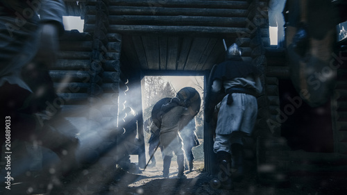 Fényképezés  Medieval Villagers Go Through Gates of Wooden Fortress Trying To Hide From Viking Attack