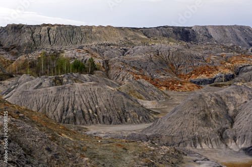 Fotografie, Obraz  landscape of spent clay quarry with eroded multi-colored slopes