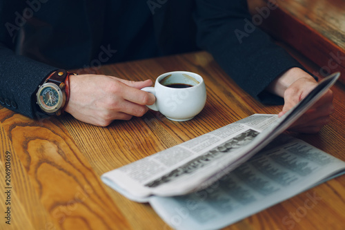 Fotografía  Man's hands close-up holding cup of coffee and a newspaper