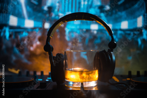 Glass with whisky with ice cube inside on dj controller at nightclub. Dj Console with club drink at music party in nightclub with disco lights.