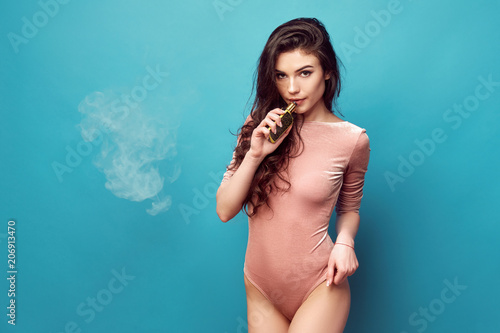 Smiling hot woman in bodysuit standing and vaping on blue background.