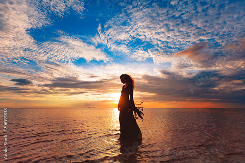 Fotografie, Obraz  Elegant woman dancing on water. Sunset and silhouette