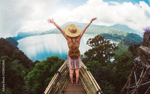 Happy female hiker standing on a cliff with her arms up in the air feeling free