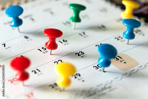 Fotomural  Various color thumb tack pins on calendar as reminder