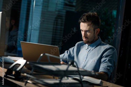 Fototapety, obrazy: Thoughtful adult man sitting at laptop in office at night.