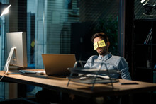 Office Worker Sleeping At Table Covering Eyes With Stickers Having Painted Eyes.