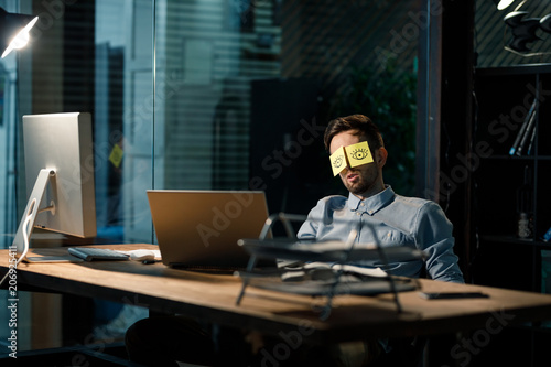 Obraz Office worker sleeping at table covering eyes with stickers having painted eyes.  - fototapety do salonu