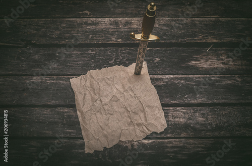 Fotografía Crumpled brown paper page parchment and the dagger blade thrust in a table