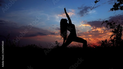 Stampa su Tela Woman doing yoga, female silhouette in evening sky background