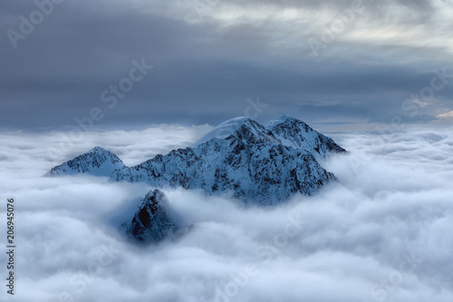 Foto auf Gartenposter Gebirge Snowy peak above the clouds